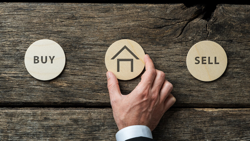 Real estate market conceptual image - hand of a businessman placing wooden cut circle with house shape on it in between Buy and Sell signs.